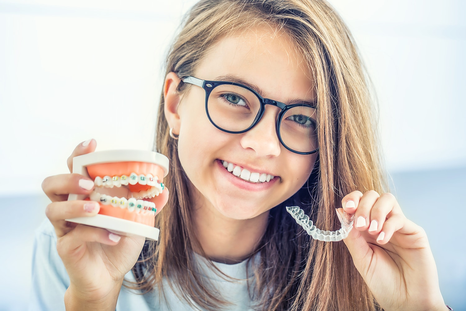 invisible braces held by young smiling girl